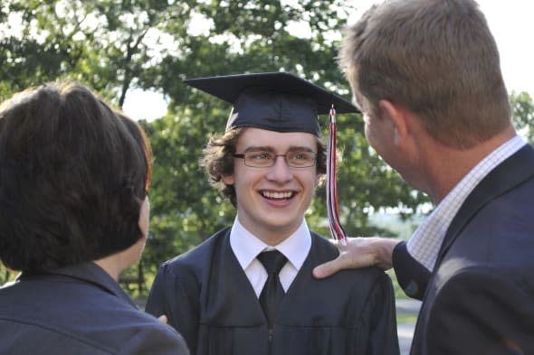 horizontal image of an excited  young graduate being congratulated by his parents. focus is on the graduate; the parents (in the
