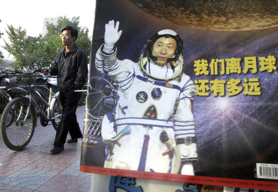 "In this photo taken Thursday, Oct 23, 2003, a man pushes his bicycle past the cover of a magazine showing China's first man in space, Yang Liwei and the Chinese characters for ""How far are we from the moon?"" at a newsstand in Beijing, China. China's Nov. 24, 2020, trip to the moon and, presumably, back is the latest milestone in the Asian powerhouse's slow but steady ascent to the stars. (AP Photo/Ng Han Guan, File)"