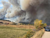 This Saturday Oct. 17, 2020, photo courtesy of Brian DeToy shows a view from the home of Brian DeToy and his wife, Sheryl Shafer, after they were forced to evacuate in Boulder, Colo. Orange skies, winds gusting up to 70 mph, smoke tornadoes and hazardous air. While it could be an apocalyptic scene out of a movie, it's become the reality of Colorado's wildfire season. (Brian DeToy via AP)