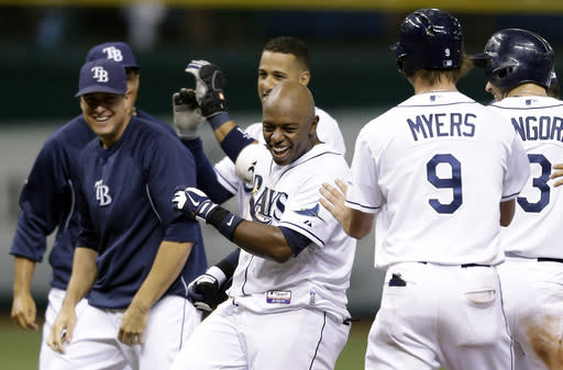 Tampa Bay Rays' Jason Bourgeois, center, celebrates with teammates after his ninth inning walk off hit off Seattle Mariners relief pitcher Danny Farquhar during a baseball game Wednesday, Aug. 14, 2013, in St. Petersburg, Fla. Rays' Matt Joyce scored on the hit. The Rays won the game 5-4. (AP Photo/Chris O'Meara)