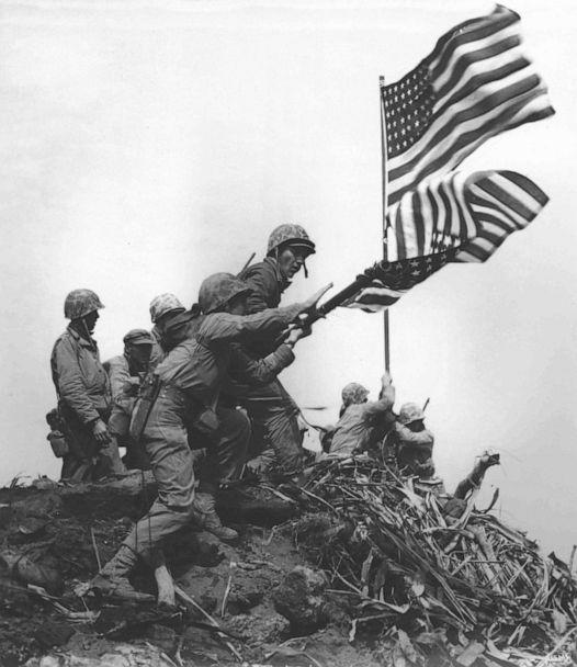 PHOTO: U.S. Marines raise a large American flag to replace a smaller flag first raised at the summit of Mount Suribachi on Iwo Jima, Feb. 23, 1945. (U.S. Marine Corps/National Archives)