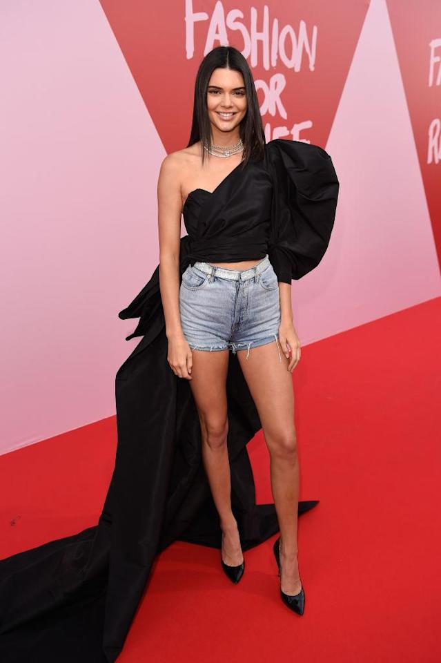 <p>The model paired a one-shoulder, black top by designer Alexandre Vauthier — that featured a long train — with denim shorts for the Fashion for Relief event on May 21, 2017 in Cannes. (Photo by Antony Jones/Getty Images) </p>