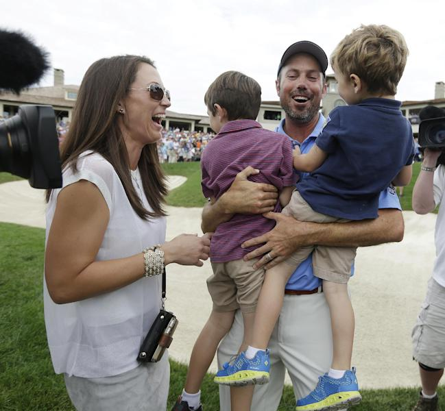 Matt Kuchar, second from right, celebrates with his wife, Sybi, left, and children, Cameron, second from left, and Carson after winning the Memorial golf tournament on Sunday, June 2, 2013, in Dublin, Ohio. (AP Photo/Darron Cummings)