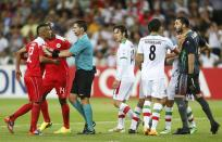 Bahrain's Faouzi Aaish (L) is separated from Iran's goalkeeper Alireza Haghighi (R) by referee Benjamin Williams of Australia as they argue following a collision in the Iranian penalty box during their Asian Cup Group C soccer match at the Rectangular stadium in Melbourne January 11, 2015. REUTERS/Brandon Malone (AUSTRALIA - Tags: SOCCER SPORT TPX IMAGES OF THE DAY)