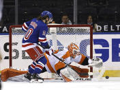 New York Rangers' Artemi Panarin (10) heads for the net as Philadelphia Flyers' Brian Elliott (37) defends in the first period of an NHL hockey game Thursday, April 22, 2021, in New York. (Elsa/Pool Photo via AP)
