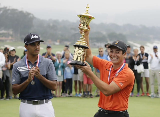 Viktor Hovland, right, of Norway, holds up the Havemeyer Trophy on the 13th green of the Pebble Beach Golf Links after winning the USGA Amateur Golf Championship Sunday, Aug. 19, 2018, in Pebble Beach, Calif. Hovland won the match against Devon Bling, left. (AP Photo/Eric Risberg)