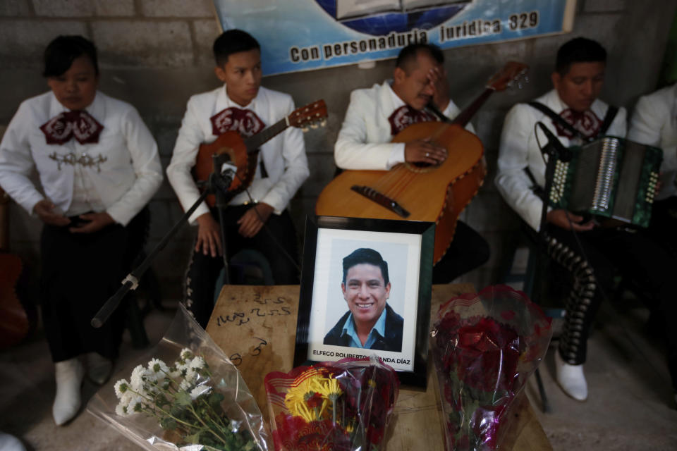A framed portrait of Elfego Miranda Diaz, one of Guatemalan migrants who was killed near the U.S.-Mexico border in January, sits on top of the coffin that contains his remains during a wake in his home in Comitancillo, Guatemala, Saturday, March 13, 2021. Thousands of residents of this Guatemalan town turned out Friday night amid tears and applause to receive the remains of 16 of their own, found piled in a charred pickup truck in Camargo, across the Rio Grande from Texas. (AP Photo/Moises Castillo)