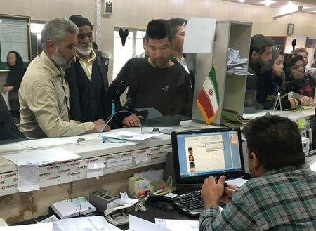 Afghan refugees submit documents at the Soleimankhani centre for refugees in Tehran