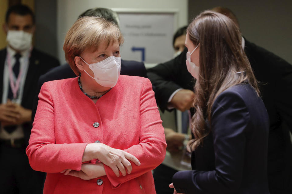 German Chancellor Angela Merkel, left, speaks with Finland's Prime Minister Sanna Marin during a round table meeting at an EU summit in Brussels, Friday, July 17, 2020. Leaders from 27 European Union nations meet face-to-face on Friday for the first time since February, despite the dangers of the coronavirus pandemic, to assess an overall budget and recovery package spread over seven years estimated at some 1.75 trillion to 1.85 trillion euros. (Stephanie Lecocq, Pool Photo via AP)