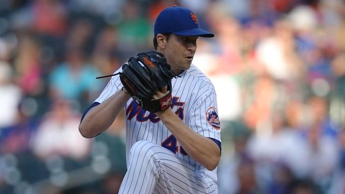 Jacob deGrom white uniform glove near his face about to deliver a pitch