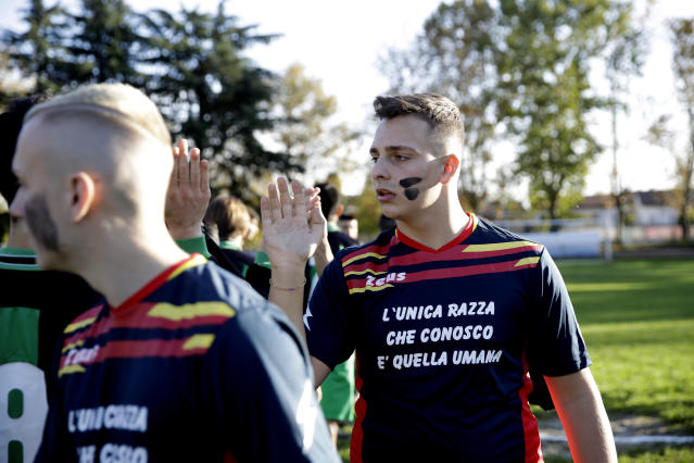 Desio players, their faces painted with black marks and wearing jerseys reading ' The only race I know is the human race 'as a symbolic sign against racism, greet their opponent team before a youth team soccer match between Desio and Sovicese, at the municipal stadium in Desio, near Milan, Italy, Saturday, Nov. 9, 2019. The initiative comes a week after an Aurora Desio team's 10-year-old player was allegedly subjected to racist abuse during a match. (AP Photo/Luca Bruno)