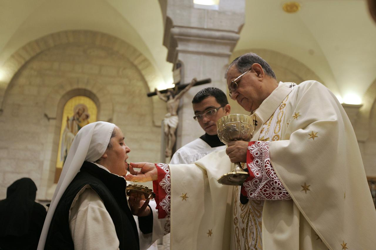 A nun takes communion from the Latin Patriarch of Jerusalem Fouad Twal during a Christmas day Mass at the Church of the Nativity, traditionally believed by Christians to be the birthplace of Jesus Christ, in the West Bank town of Bethlehem, Sunday, Dec. 25, 2011. Hundreds of Christian faithful, defying lashing rains and wind, celebrated Christmas Mass at Jesus' traditional birthplace on Sunday, spirits high despite the gloomy weather. (AP Photo/Majdi Mohammed)