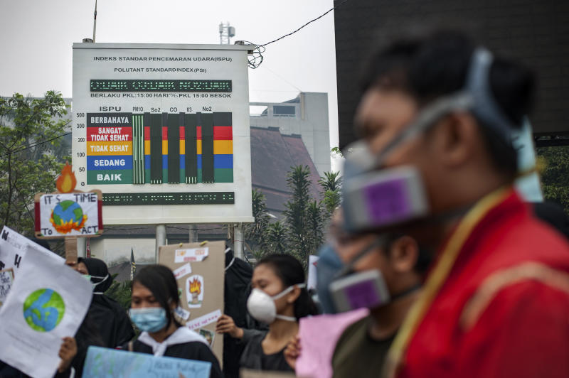 Activists stage a protest urging the government to speed up their action to tackle forest fires as an information board showing a very unhealthy level in Palangkaraya, Central Kalimantan, Indonesia, Friday, Sept. 20, 2019. Haze blown by monsoon winds from fires in Indonesia has begun affecting some areas of the Philippines and raised concerns about aviation safety and possible health risks, an official said Friday. (AP Photo/Fauzy Chaniago)