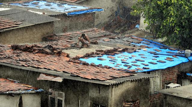 An Indian man tends to his leaking roof during a heavy downpour in Mumbai on June 9, 2013. India's 235 million farmers still rely on the erratic rains to soak around 60 percent of the country's farmland -- despite calls for the government to improve irrigation and water-harvesting methods to ensure more stable crop output.