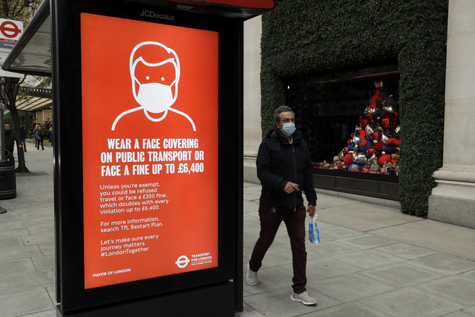 A person wearing a face mask walks past a sign on a bus stop warning people to wear a face covering on public transport or face a fine, outside the Selfridges department store on Oxford Street during England's second coronavirus lockdown, in London, Monday, Nov. 23, 2020. British Prime Minister Boris Johnson has announced plans for strict regional measures to combat COVID-19 after England's second lockdown ends Dec. 2, sparking a rebellion by members of his own party who say the move may do more harm than good. (AP Photo/Matt Dunham)
