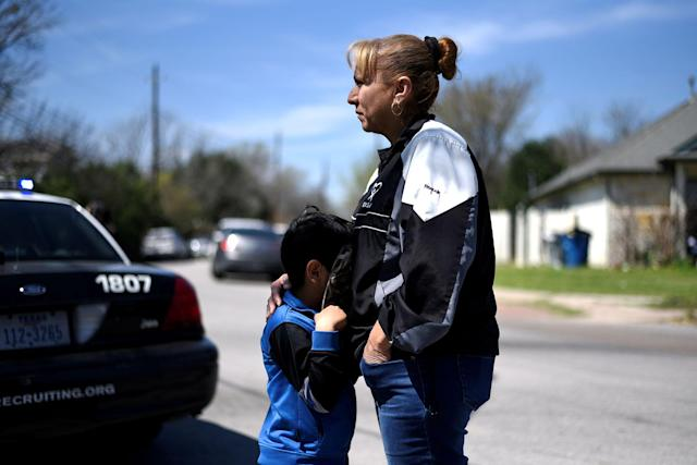 <p>Isaac Machado hides behind his hat against his mother Delores just outside the scene of an explosion on Galindo Street in Austin, Texas, March 12, 2018. (Photo: Sergio Flores/Reuters) </p>