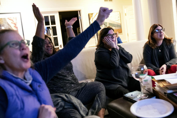 """FILE - In this Tuesday, Nov. 3, 2020 file photo, supporters of Democratic presidential candidate Joe Biden, from left, Kimber Bishop-Yanke, Leslie Esters-Redwine, Lori Goldman and Mimi Miletic watch election results in Bloomfield Hills, Mich. In suburban Michigan, a coalition of suburban women achieved what they set out to do _ help evict Donald Trump from the White House. But Goldman, who runs the group Fems for Dems, can't shake the sense that their mission now is more critical than it's ever been. """"We got rid of this blight, this cancer,"""" said Goldman, 61. """"We cut him out. But we know that cancer has spread, it's spread to soft tissue, other organs. And now we have to save the rest of the body."""" (AP Photo/David Goldman)"""