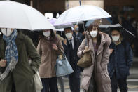 People wearing face masks to protect against the spread of the coronavirus walk at a crossing in Tokyo, Monday, Feb. 15, 2021. Tokyo is under state of emergency as the government seeks to stop a surge of new coronavirus infections. (AP Photo/Koji Sasahara)