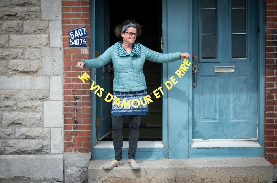 """Valerie Menguy holds her banner """"I live on love and laughter"""" by artist Patsy Van Roost on May 6, 2020, in Montreal. - Artist Patsy Van Roost is brightening up Montreal balconies and putting smiles on pandemic-weary passers-by with a litany of personalized messages on multicolored banners hung across the city. """"The idea is to spread a little love for people during their solo walks,"""" she told AFP. (Photo by Sebastien St-Jean / AFP) (Photo by SEBASTIEN ST-JEAN/AFP via Getty Images)"""