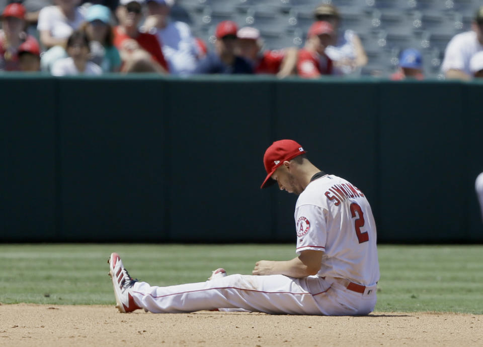 Los Angeles Angels shortstop Andrelton Simmons takes a seat after fielding a ground ball hit by Detroit Tigers' Gordon Beckham, but couldn't get up to make the throw during the fifth inning of a baseball game in Anaheim, Calif., Wednesday, July 31, 2019. (AP Photo/Alex Gallardo)