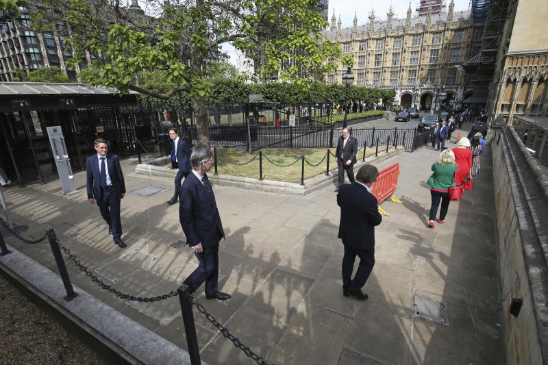 UK lawmakers including Leader of the House of Commons Jacob Rees-Mogg, center left, queue outside the Houses of Commons in Westminster, London, Tuesday June 2, 2020. Prime Minister Boris Johnson's Conservative government faced a rebellion from some of its own legislators on Tuesday after it summoned Members of Parliament back to London and prepared to scrap a remote-voting system used during a nationwide coronavirus lockdown. (Jonathan Brady/PA via AP)