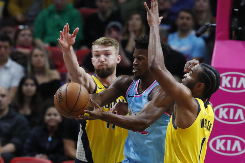 Miami Heat forward Jimmy Butler, center, loses control of the ball as he is guarded by Indiana Pacers forwards Domantas Sabonis, left, and T.J. Warren during the first half of an NBA basketball game Friday, Dec. 27, 2019, in Miami. (AP Photo/Wilfredo Lee)