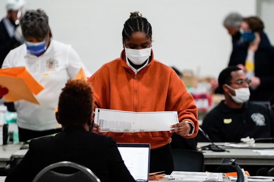 Election workers check ballots.