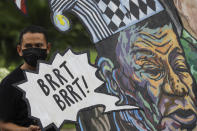 A protester stands beside a caricature of Philippine President Rodrigo Duterte before marching towards the House of Representatives where he is set to deliver his final State of the Nation Address in Quezon city, Philippines on Monday, July 26, 2021. Duterte is winding down his six-year term amid a raging pandemic and a battered economy. (AP Photo/Gerard Carreon)