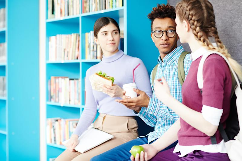 Three friendly groupmates with drinks and snack having talk at lunch break in college library