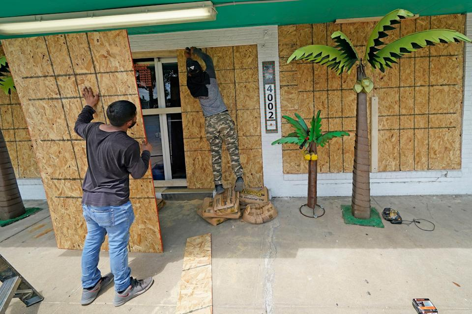 Issac Alvarado, right, and Kevin Enriquez board up windows on Tuesday at Bayside Chic, a coastal decor store in Galveston, Texas, ahead of Hurricane Laura's arrival in the Gulf Coast.