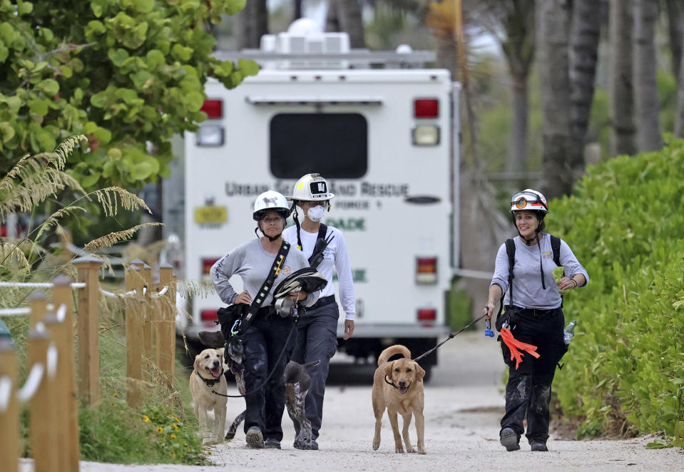 Fire rescue personnel conducting search and rescue walk back with their dogs to Champlain Towers South Condo after a wing of the multistory building collapsed, in Surfside, Fla., Thursday, June 24, 2021. (David Santiago/Miami Herald via AP)