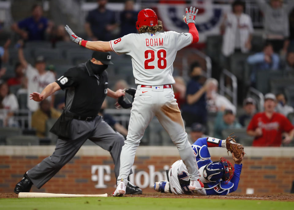 Alec Bohm of the Philadelphia Phillies slides and beats the tag of Travis d'Arnaud of the Atlanta Braves