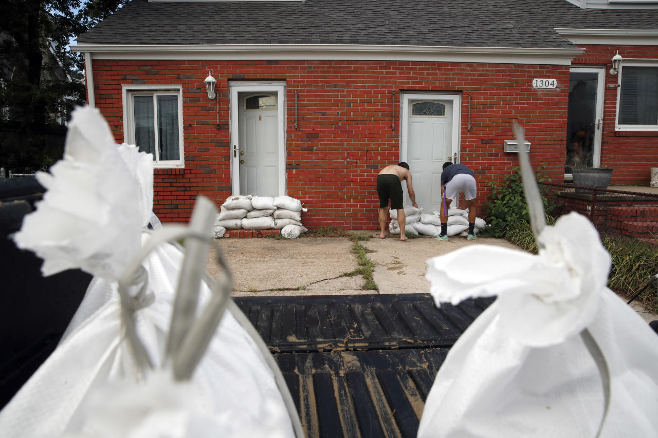 <p>Adam Bazemore, left, and Sebastian Silva, place sandbags in the doorways, Tuesday, Sept. 11, 2018, in the Willoughby Spit area of Norfolk, Va., as they make preparations for Hurricane Florence. (Photo: Alex Brandon/AP) </p>