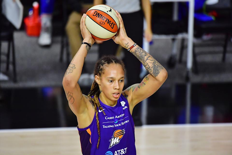 Brittney Griner in a purple Mercury jersey holds a basketball above her head.