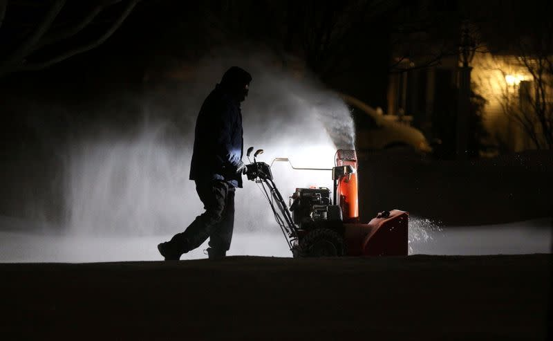 Roger Hake gets an assist from his truck lights as he clears snow from his driveway before the sun comes up in Webster