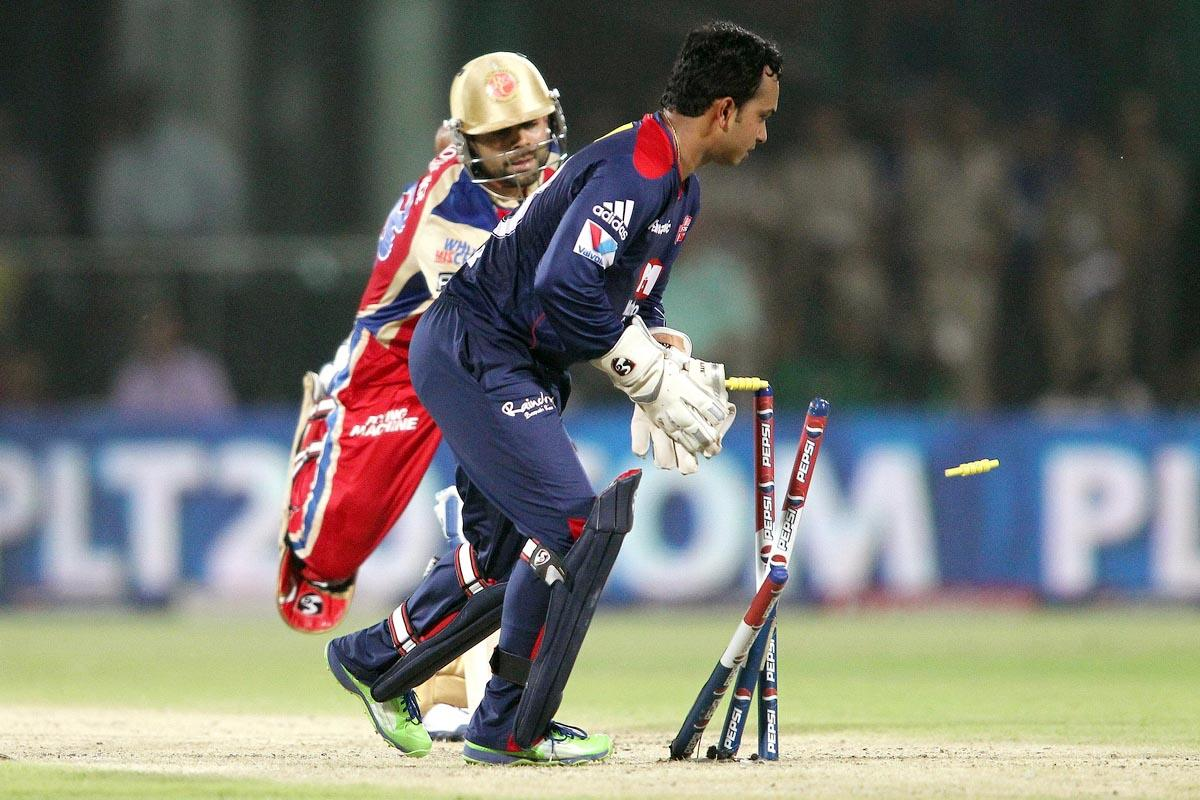 Kedar Jadhav of Delhi Daredevils breaks the stumps to run out Royal Challengers Bangalore captain Virat Kohli for 99 during match 57 of the Pepsi Indian Premier League between Delhi Daredevils and the Royal Challengers Bangalore held at the Feroz Shah Kotla Stadium, Delhi on the 10th May 2013. (BCCI)