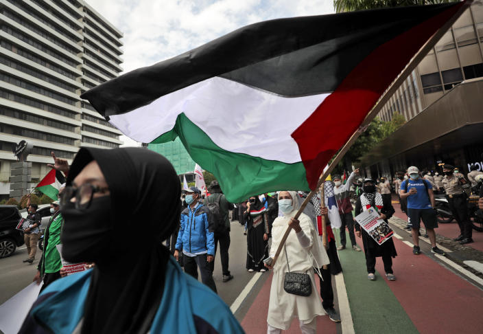 A Muslim woman waves a Palestinian flag during a rally condemning Israeli attacks on the Palestinians in Jakarta, Indonesia, Tuesday, May 18, 2021. (AP Photo/Dita Alangkara)