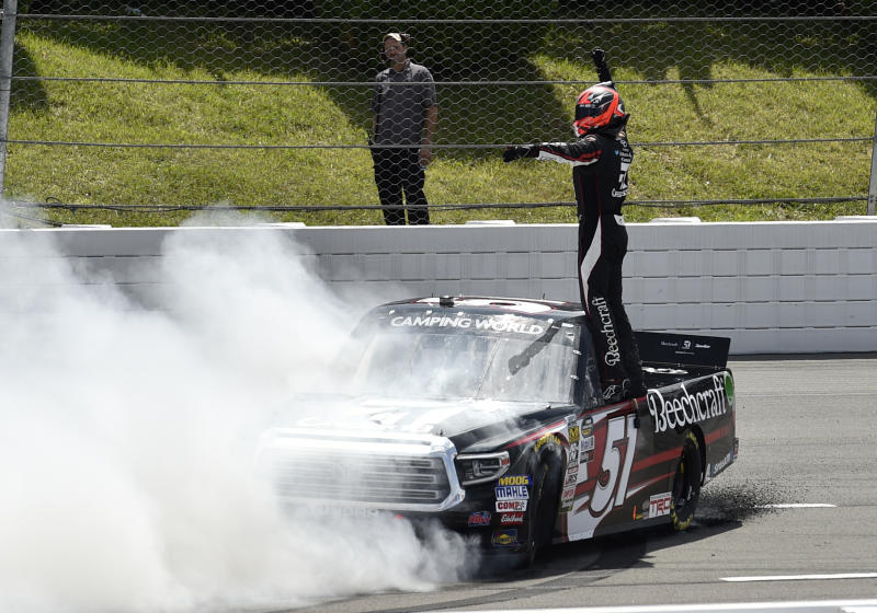 """FILE - In this July 28, 2018, file photo, Kyle Busch celebrates after winning a NASCAR Truck Series auto race in Long Pond, Pa. Busch says, """"Bring it on."""" Chase Elliott and Kyle Larson are the latest topflight drivers to accept the challenge of Kevin Harvick, who has offered half of a $100,000 bounty to any Cup Series driver who can beat the versatile Busch in a Truck Series race this year. (AP Photo/Derik Hamilton, File)"""
