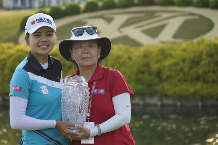 Wei-Ling Hsu, left, of Taiwan, holds the winner's trophy with her mother, Wei-chia Lu, as she celebrates afterwinning the LPGA Tour's Pure Silk Championship golf tournament in Williamsburg, Va., Sunday, May 23, 2021. (AP Photo/Steve Helber)