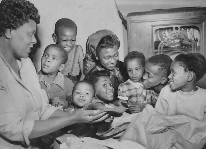The Roy Arnold family looks over some of the Christmas gifts purchased with a $100 gift from an unknown benefactor in 1954. Pictured from left are mother Helen Arnold with children Gary, 4, John, 6, Gerald, 18 months, Gale, 7, Cathy, 13, Carla, 3, Royal, 10, and Mona, 8.