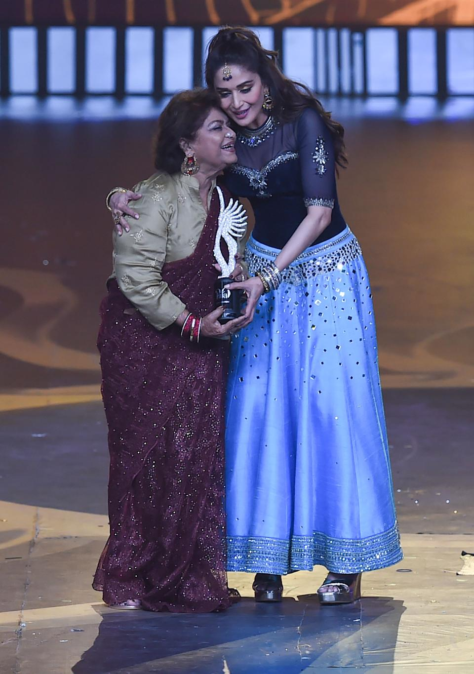 Bollywood choreographer Saroj Khan (L) hugs actress Madhuri Dixit after receiving a special award for Best Choreographer in Last 20 Years, during the 20th International Indian Film Academy (IIFA) Awards at NSCI Dome in Mumbai on September 18, 2019. (Photo by INDRANIL MUKHERJEE / AFP)        (Photo credit should read INDRANIL MUKHERJEE/AFP via Getty Images)
