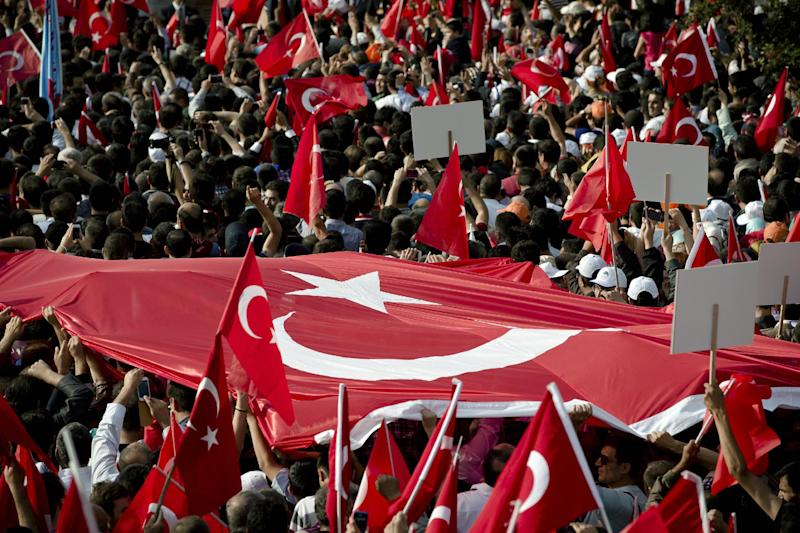 Supporters of Turkish Prime Minister Recep Tayyip Erdogan carry a large Turkish flag during his speech in Ankara, Turkey, Sunday, June 9, 2013.(AP Photo/Vadim Ghirda)