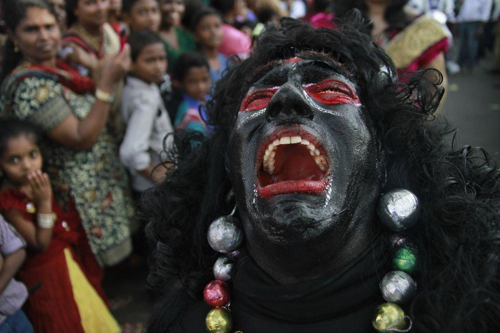 A reveler dressed as a demon reacts as he performs during the 29th Cochin Carnival at Fort Kochi, in the southern Indian city of Kochi January 1, 2013. The carnival is held annually to welcome the start of a new year.