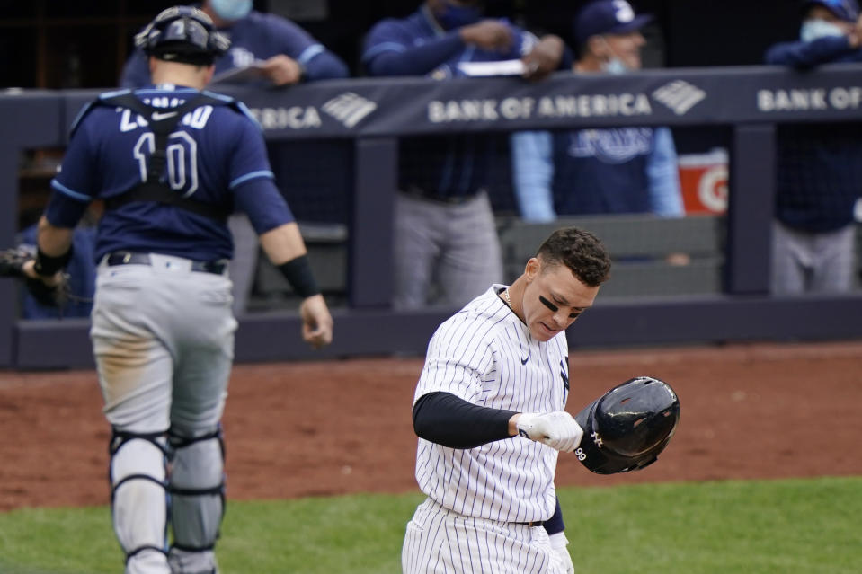 New York Yankees Aaron Judge tosses his batting helmet after striking out stranding two runners on base during the fifth inning of a baseball game against the Tampa Bay Rays, Sunday, April 18, 2021, at Yankee Stadium in New York. Rays catcher Mike Zunino (10) heads to the dugout. (AP Photo/Kathy Willens)