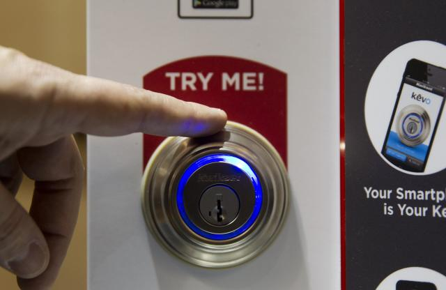 A Kevo smart lock is demonstrated during the 2015 International Consumer Electronics Show (CES) in Las Vegas, Nevada January 4, 2015. The lock, which opens with a smart phone App and a touch, is smart enough to know what side of the door you are on and won't accidentally unlock the door when you are inside. A new subscription service offers unlimited e-keys and other benefits, a representative said. REUTERS/Steve Marcus (UNITED STATES - Tags: SCIENCE TECHNOLOGY BUSINESS)