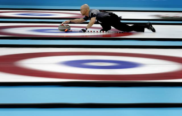Canada's Ryan Fry delivers the rock during the men's curling gold medal game against Britain at the 2014 Winter Olympics Friday, Feb. 21, 2014, in Sochi, Russia. (AP Photo/Wong Maye-E)