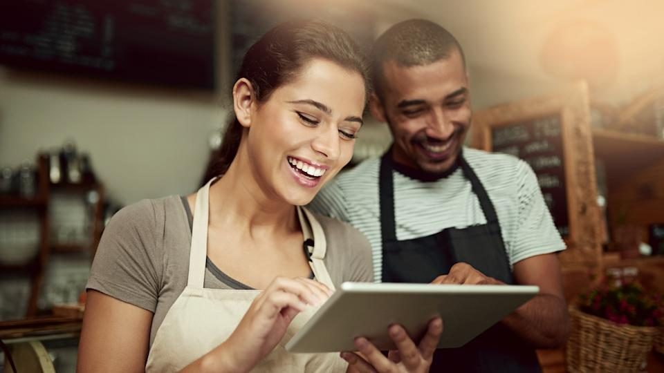 A female and a male cafe worker looking at a tablet computer smiling.