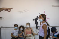 """People wait to have their children tested for a COVID-19 antibody test in Hadera, Israel, Monday, Aug. 23, 2021. Ahead of the opening of the school year on Sept. 1, the Israeli army's Home Front Command is conducting serology tests on children age 3-12 who have not yet tested positive for coronavirus and are not yet listed as recovered, to see if they have antibodies. If a child tests positive for coronavirus antibodies, they can be issued a """"green pass,"""" allowing them to attend classes in-person. (AP Photo/Ariel Schalit)"""