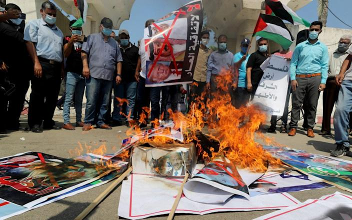 Palestinians burn pictures depicting U.S. President Donald Trump and Bahrain's King Hamad bin Isa Al Khalifa during a protest against the deal with Israel to normalise relations - Mohammed Salem/Reuters