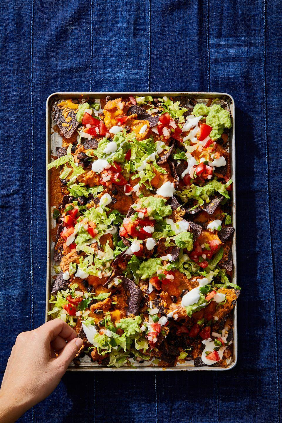 """<p>With refried and black beans (and lots of cheese!), you won't miss the meat on these easy nachos.</p><p><em><a href=""""https://www.goodhousekeeping.com/food-recipes/a29960234/how-to-make-nachos-recipe/"""" rel=""""nofollow noopener"""" target=""""_blank"""" data-ylk=""""slk:Get the recipe for Double Bean Sheet Pan Nachos »"""" class=""""link rapid-noclick-resp"""">Get the recipe for Double Bean Sheet Pan Nachos »</a></em></p><p><strong>RELATED: </strong><a href=""""https://www.goodhousekeeping.com/food-recipes/g25727072/vegetarian-super-bowl-recipes/"""" rel=""""nofollow noopener"""" target=""""_blank"""" data-ylk=""""slk:30 Vegetarian Super Bowl Recipes That Prove Game Day Can Be Meat-Free"""" class=""""link rapid-noclick-resp"""">30 Vegetarian Super Bowl Recipes That Prove Game Day Can Be Meat-Free</a><br></p>"""